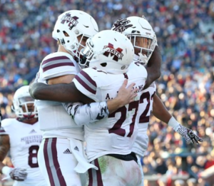 Williams celebrating with MSU teammates during their Egg Bowl victory